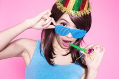 Woman take noisemaker. Young woman with party hat and noisemaker on the pink background royalty free stock photo