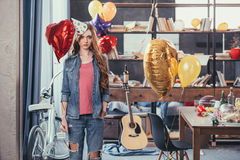 Young woman in party hat standing in messy room after party Stock Images