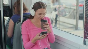 Young woman passenger enjoying trip at the public transport, sitting with headphones near the window in the modern tram. Young woman passenger enjoying trip at stock video footage