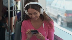 Young woman passenger enjoying trip at the public transport, sitting with headphones near the window in the modern tram. Young woman passenger enjoying trip at stock footage