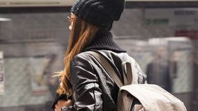 Young woman passenger in public train station in city stock photo