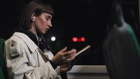Young woman or passenger reading book and listen music sitting in public transport, steadicam shot. Slow motion. City. Lights background. Commuter, student stock video footage