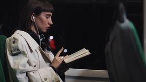 Young woman or passenger reading book and listen music sitting in public transport, steadicam shot. Slow motion. City. Lights background. Commuter, student stock footage