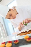 Young woman pastry cook preparing a cake Stock Images