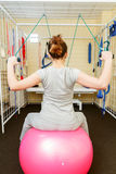 Young woman patient doing physical exercises in a rehabilitation study. Stock Photo