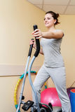 Young woman patient doing physical exercises in a rehabilitation study.young woman doing exercise on a stationary bike. Royalty Free Stock Photos
