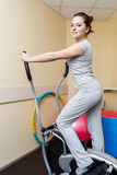 Young woman patient doing physical exercises in a rehabilitation study.young woman doing exercise on a stationary bike. Royalty Free Stock Photography