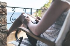 Woman on patio by sea writing or taking notes with pen Stock Photos
