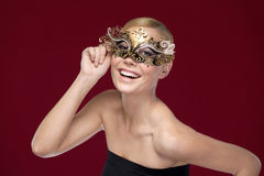 Young woman with patterned masquerade mask Stock Photos