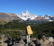 A young woman pauses on the trail to wonder at Mount Fitz Roy royalty free stock image
