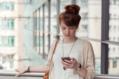 Young woman pausing to check an sms Royalty Free Stock Photography