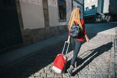 Young woman on the pavement with a red suitcase. Rear view. Stock Photos