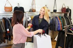 Young woman paying by credit card. Young women paying to shop assistant by credit card and receiving shopping bags in store. Credit card shopping concept Stock Photography