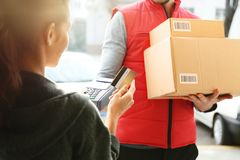 Young woman paying for parcels received from courier. Closeup Royalty Free Stock Images