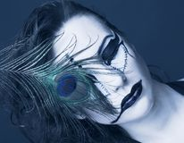 Young woman with peacock  feather. Young woman with creative make-up and peacock  feather Royalty Free Stock Image