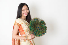 Young woman with peacock feather fan in Indian sari dress. Portrait of young mixed race Indian Chinese girl in traditional sari dress, holding peacock feathers Royalty Free Stock Photo