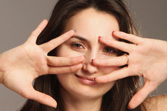 Young woman peeking through fingers Royalty Free Stock Images