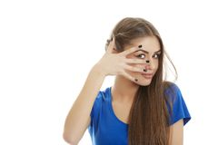 Young woman peeking through fingers Stock Photo
