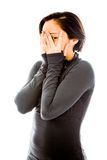 Young woman peeking through hands covering face Stock Image