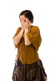 Young woman peeking through hands covering face Royalty Free Stock Image