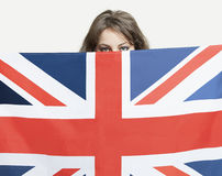 Young woman peeking over British flag against gray background Royalty Free Stock Photos