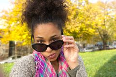 Young woman peeking over sunglasses. Close up portrait of a young woman peeking over sunglasses Royalty Free Stock Photos