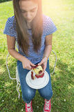 Young woman peeling an apple Stock Photo