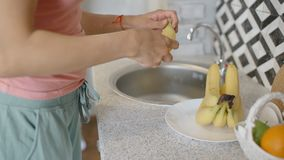 Young woman is peeling banana, standing at table in home kitchen. Young woman is peeling banana, standing at table in home kitchen, busy housewife in casual stock video footage