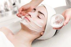 Young woman peeling foam mask applying on face Stock Image