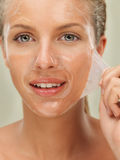 Young woman peeling off a facial mask Stock Photography
