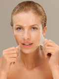 Young woman peeling off a facial mask smiling Royalty Free Stock Photos