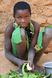 Young woman peels cooking plantains, Tanzania Royalty Free Stock Images