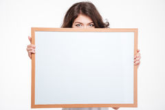 Young woman peeping from blank board Royalty Free Stock Photos