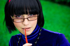 Young woman with pen. Thoughtful young woman with black hair chewing on end of pen outdoors; green nature background Royalty Free Stock Images