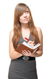 Young woman with pen and datebook deep in thought. Cute young woman in nice dress with pen and open  personal organizer deep in thought Royalty Free Stock Image