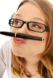 Young woman with pen on mouth Royalty Free Stock Photos