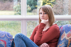 Young woman is pensively looking at the camera. Stock Photos