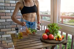 Young woman with perfect abdominals cooks food in a kitchen. She has a muscular body and a diet food on his table stock photo