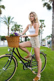 Young woman with a perfect figure stands with her retro bike in the park on green grass while enjoying a rest after riding Stock Photos