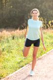 Young woman with perfect slim body stretching her leg stock photography