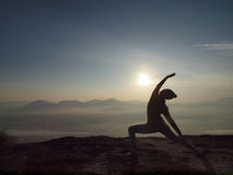 Young woman perform Yoga on the cliff in morning Stock Photography