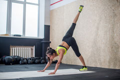 Young woman performin yoga in gym, fit female doing stretching exercises on mat Royalty Free Stock Photos