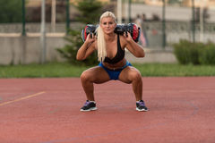 Young Woman Performing Bag Squat Exercise Outdoor Stock Photos