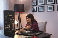 Woman dusting computer components. Young woman performing a computer maintenance, clearing the dust out of the components royalty free stock photo