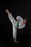Young Woman Performing Tae Kwon Do High Kick. A young woman performs a martial arts high kick with agression royalty free stock photography