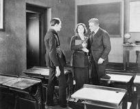 Young woman performing for two men in a class room Royalty Free Stock Photo