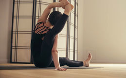 A young woman performing yoga-asanas in the hall. Stock Photography