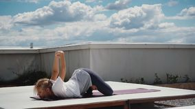 Young woman performs advanced asanas of Hatha yoga is lying on yoga mat. Young woman performs advanced asanas of Hatha yoga is lying on stomach, on yoga mat stock footage