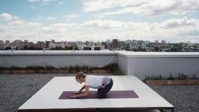 Young woman performs comlex asanas of hatha yoga is lying on yoga mat. Young woman performs comlex asanas of hatha yoga is lying on stomach, on yoga mat. girl stock footage