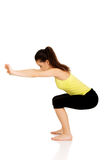Young woman performs squats. Royalty Free Stock Image